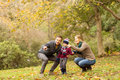 Young couple pointing something to their little boy on an autumns day Stock Image