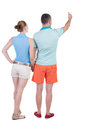 Young couple pointing at wal back view woman and man rear people collection backside of person isolated over white Stock Photography