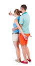 Young couple pointing at wal back view woman and man rear people collection backside of person isolated over white Stock Photos