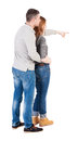Young couple pointing at wal back view woman and man rear people collection isolated over white background hugging his wife shows Royalty Free Stock Photos