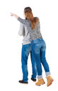 Young couple pointing at wal back view woman and man rear people collection she stood on tiptoes shows something in front of Stock Image