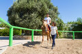 Young couple practices horseback riding lessons with a brown blond purebred mare in the club arena Royalty Free Stock Photos