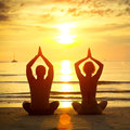 Young couple practicing yoga on the beach Royalty Free Stock Image