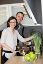 Young couple preparing dinner standing close together over the stove looking at the camera with cheerful smiles Stock Photography