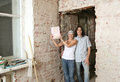 Young couple with property deed in unrepair apartment Stock Photo