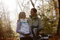 A young couple pushing a stroller in the park, smiling Royalty Free Stock Photo