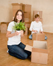 Young couple holding cardboard boxes for moving into a new house