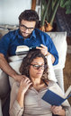 Young couple reading book on couch at home Royalty Free Stock Photo