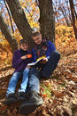 Young couple reading book under the old tree Royalty Free Stock Photo