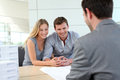 Young couple with realtor in agency real estate talking to construction planner Royalty Free Stock Image