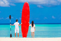 Young couple with red surfboard during tropical Royalty Free Stock Photo