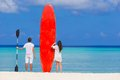 Young couple with red surfboard on white beach Royalty Free Stock Photo
