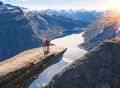 Young couple relax on Trolltunga. Happy girl enjoy beautiful lake and good weather in Norway. Royalty Free Stock Photo