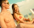 Young couple relaxing on a beach deck chairs Stock Photo