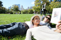 Young couple relaxing in central park lying in grass Royalty Free Stock Photo