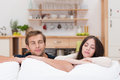 Young couple relaxing with closed eyes attractive and blissful smiles their arms resting on top of the sofa cushions Stock Image