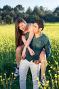 Young couple relaxing in the countryside with men carrying his girlfriend on his back a piggy back ride through a field of Stock Photography
