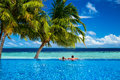 Young couple relaxing in infinity pool under coco palms front of tropical landscape Royalty Free Stock Photo