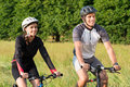 Young couple riding bicycle in meadow happy sportive man and woman Royalty Free Stock Image