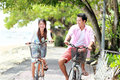 Young couple riding bicycle together happy asian laughing Stock Photos