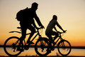 Young couple riding bicycles at sunset. Royalty Free Stock Photography