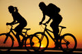 Young couple riding bicycles at sunset Royalty Free Stock Photos