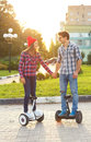 A young couple riding hoverboard electrical scooter personal eco transport gyro smart balance wheel new modern Royalty Free Stock Photography
