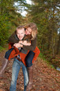 Young couple is riding piggyback happy having a nice time in october Stock Photo