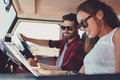 Young couple on roadtrip reading map for directions side view of a men and women in the car going Royalty Free Stock Images