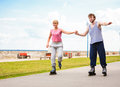Young couple rollerblading in park holding hands. Royalty Free Stock Photo
