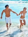 Young couple running at the beach Royalty Free Stock Photo