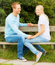 Young couple seated on a bench in the garden Stock Photo