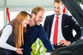 Young couple and seller with auto in car dealership or salesman clients or customers presenting the engine performance of new used Stock Photo