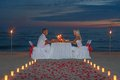 Young couple share a romantic dinner with candles torches and way or rose petals on sea sandy beach against sunset wedding day Stock Photography