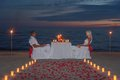 Young couple share a romantic dinner with candles and way or rose torches petals on sea sandy beach against sunset wedding day Royalty Free Stock Photography