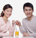 Young couple sharing a glass of orange juice studio shot Royalty Free Stock Image