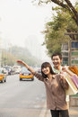Young couple with shopping bags hailing a taxicab in beijing Royalty Free Stock Images