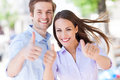 Young couple showing thumbs up outdoors Royalty Free Stock Photo