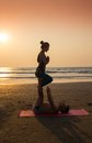 Young couple sitting on the beach yoga practice a of sea in lotus position at sunset Royalty Free Stock Photography
