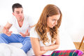 Young couple sitting on the bed because of relationship difficul difficulties lying in having sexual disfunction confused Royalty Free Stock Image