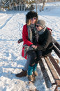 Young couple sitting on a bench in a park in winter love and smiling Royalty Free Stock Photography