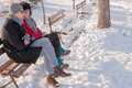 Young couple sitting on bench in winter park and talking Royalty Free Stock Photos