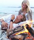 Young couple sitting by bonfire at beach in summer Stock Photography