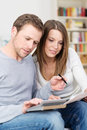 Young couple sitting checking their finances together as the husband checks figures on a document held by his wife Stock Photography
