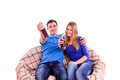 Young couple sitting on a couch and drinking a soda isolated Stock Images
