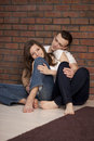 Young couple sitting embracing floor Stock Image