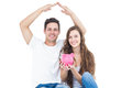 Young couple sitting on floor with piggy bank
