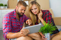 Young couple sitting on the floor with tablet pc and choosing fu
