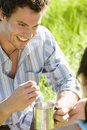 Young couple sitting on grass focus on man holding camping mug smiling close up men Stock Photo