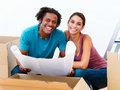 Young couple sitting in the middle of moving boxes Stock Images